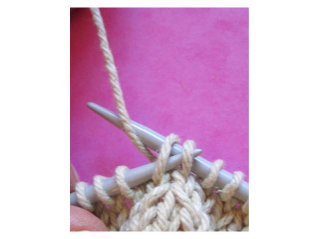 Paso 2. Insertar la aguja izquierda en los 2 puntos pasados por las hebras de delante. Rodear la aguja derecha con el hilo del ovillo.